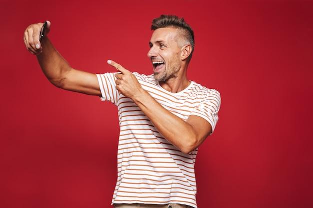 Ritratto di un uomo allegro in piedi sul rosso