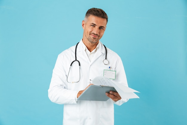 Ritratto di allegro medico con stetoscopio in possesso di tessera sanitaria, in piedi isolato sopra la parete blu