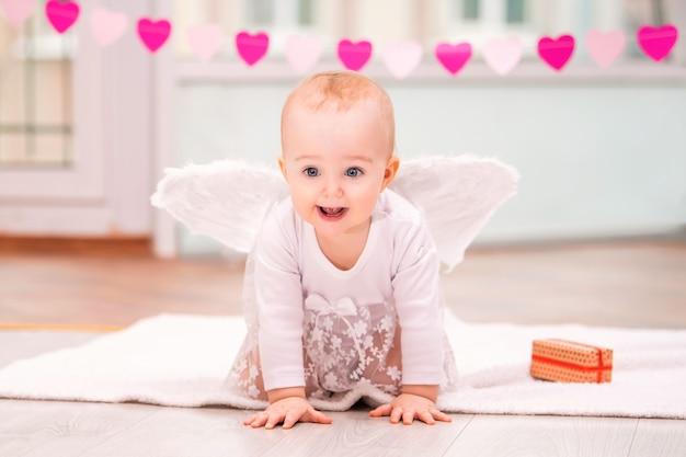Ritratto di un bambino allegro malizioso con ali d'angelo bianche che strisciano verso lo spettatore