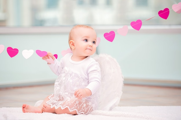 Ritratto di un bambino allegro malizioso con ali d'angelo bianco che tocca un ornamento del cuore