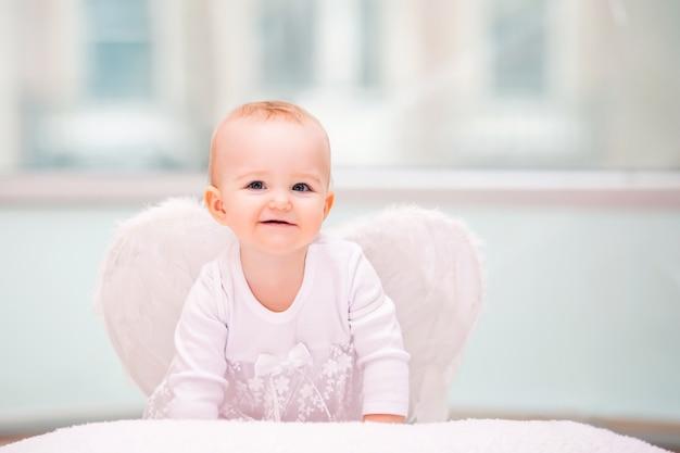 Ritratto di un bambino allegro malizioso con ali d'angelo bianche
