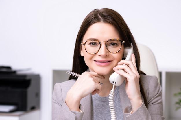 Ritratto di signora moderna allegra in bicchieri tenendo la penna e rispondere alla telefonata mentre si lavora in ufficio