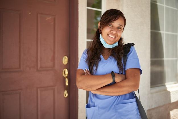Ritratto di un'infermiera allegra davanti a casa