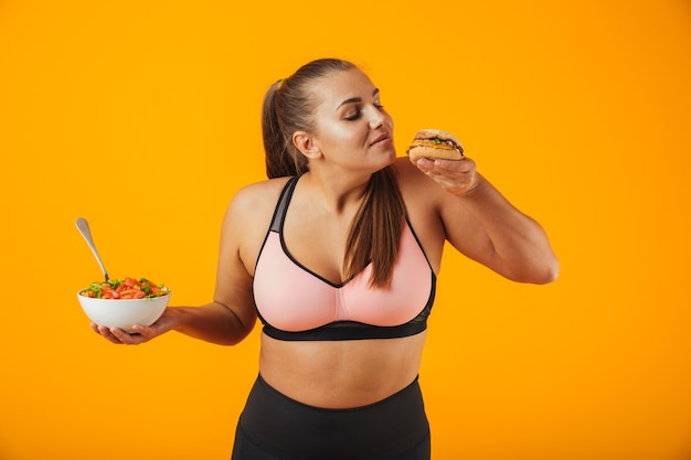 Ritratto di una donna allegra di forma fisica in sovrappeso che indossa abbigliamento sportivo in piedi isolato sopra il muro giallo, tenendo una ciotola con insalata e un hamburger
