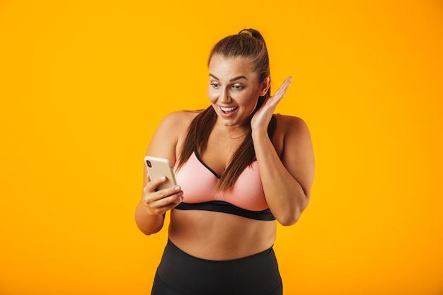 Ritratto di una donna allegra fitness in sovrappeso che indossa abbigliamento sportivo in piedi isolato sopra il muro giallo, tenendo il telefono cellulare