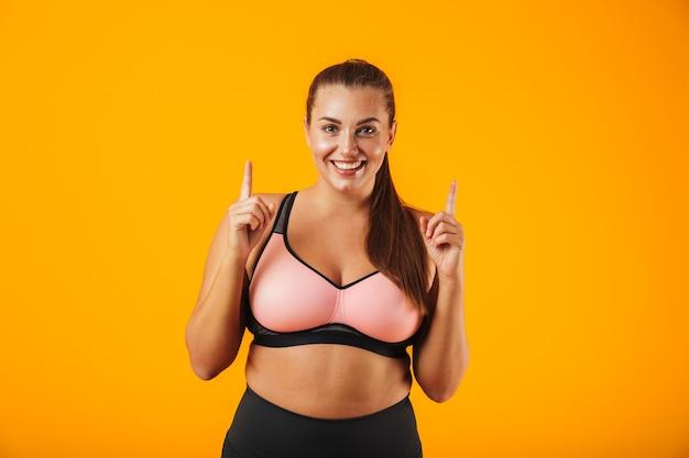 Ritratto di una donna allegra fitness in sovrappeso che indossa abbigliamento sportivo in piedi isolato sopra la parete gialla, puntando le dita nello spazio della copia