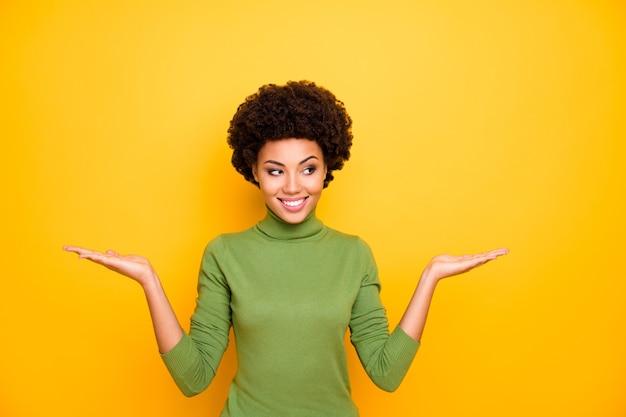 Ritratto di ragazza alla moda elegante ondulata riccia positiva allegra che tiene due oggetti con le mani sorridenti a trentadue denti in dolcevita verde.