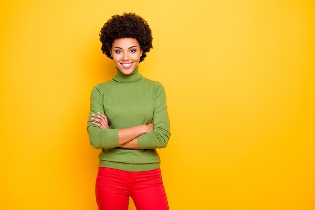 Ritratto di allegro positivo carino bella donna piuttosto affascinante con le mani giunte in pantaloni rossi sorridendo a trentadue denti vicino allo spazio vuoto.