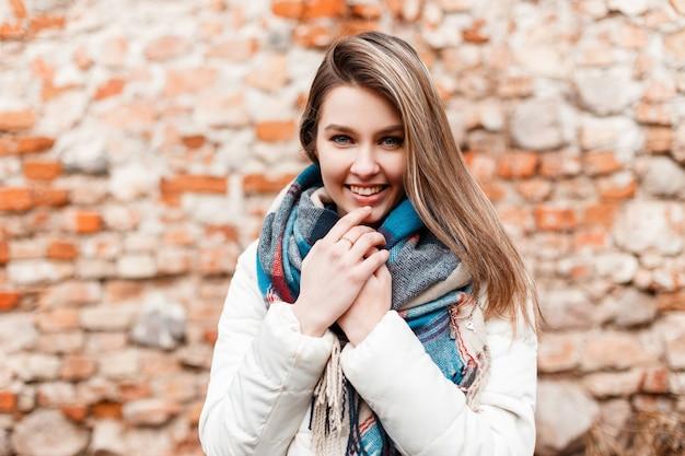Ritratto di una giovane donna felice positiva allegra con un bel sorriso in una giacca elegante bianca con una sciarpa calda alla moda di lana sullo sfondo di un vecchio muro di mattoni. bella ragazza sorridente