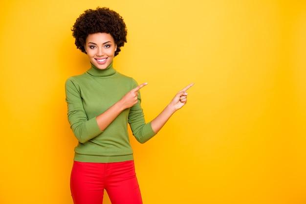 Ritratto di donna allegra bella cura positiva positiva bella che punta nello spazio vuoto in pantaloni rossi con gli indici.