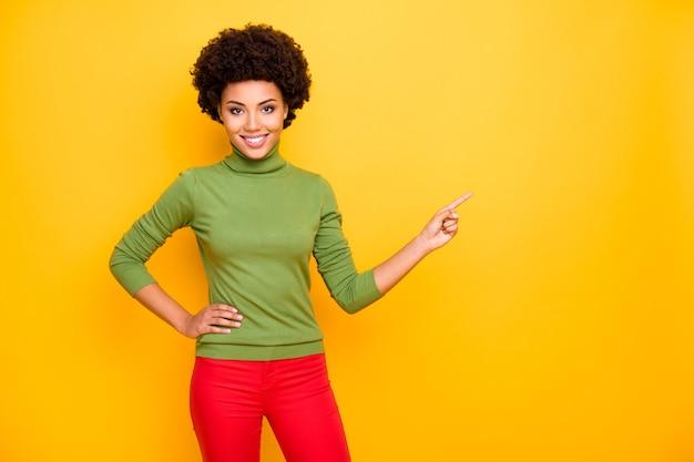 Ritratto di donna allegra piuttosto carina positiva che punta nello spazio vuoto alle vendite in pantaloni rossi.