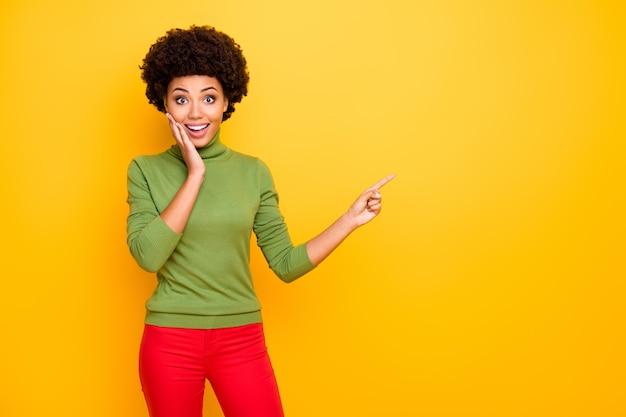 Ritratto di donna allegra piuttosto dolce positiva che punta nello spazio vuoto con l'indice in pantaloni rossi.