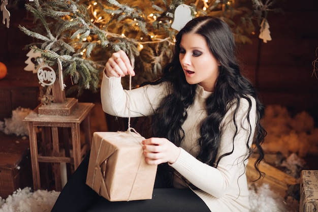 Ritratto di donna allegra e positiva con lunghi capelli scuri in maglione, jeans e calzini caldi che tiene regalo avvolto per natale mentre era seduto sotto l'albero di natale decorato e nevicata
