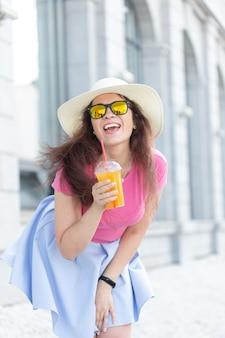 Ritratto di una giovane donna allegra positiva in un cappello e occhiali con succo nelle sue mani in giro per la città in una soleggiata giornata estiva calda. il concetto di umore spensierato.