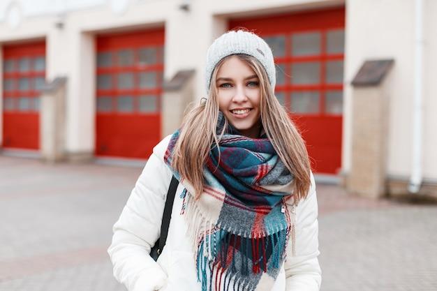 Ritratto di una giovane donna allegra positiva con un dolce sorriso con una calda sciarpa a scacchi elegante e una giacca bianca alla moda sullo sfondo di un edificio con porte rosse. la ragazza sorride.