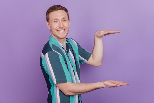 Ritratto di allegro promotore consigliere le mani del ragazzo tengono misura lo spazio vuoto su sfondo viola