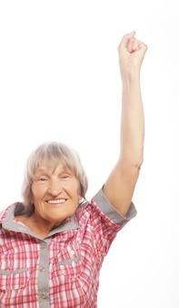 Ritratto di una donna maggiore allegra gesticolando vittoria su uno sfondo bianco