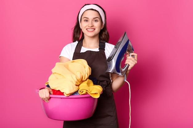 Ritratto della casalinga sincera allegra che esamina direttamente la macchina fotografica
