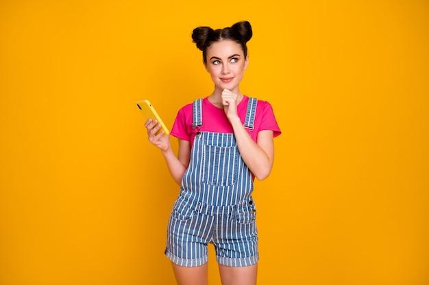 Ritratto di una ragazza allegra e intelligente che usa una cella isolata su uno sfondo di colore giallo