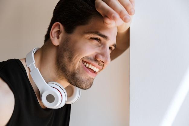 Ritratto di un giovane sportivo felice sorridente allegro in piedi vicino alla finestra con le cuffie sul collo.