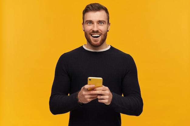 Ritratto di uomo allegro e sorridente con barba e capelli castani. ha il piercing. indossare un maglione nero. in possesso di uno smartphone, isolato su una parete gialla