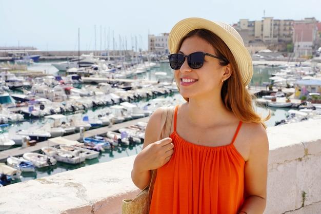Ritratto di allegra donna sorridente con abito arancione camminando sul lungomare del porto di bisceglie, puglia, italy