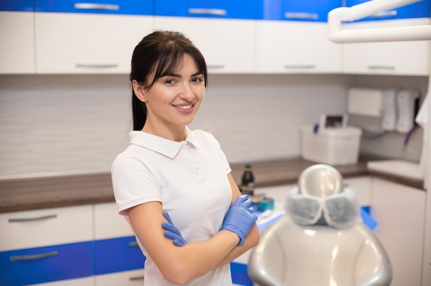 Ritratto di un giovane dentista sorridente allegro in piedi vicino a una poltrona odontoiatrica con le braccia incrociate.