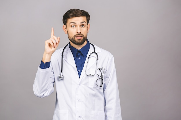 Ritratto di giovane medico sorridente allegro con lo stetoscopio sopra il collo in cappotto medico