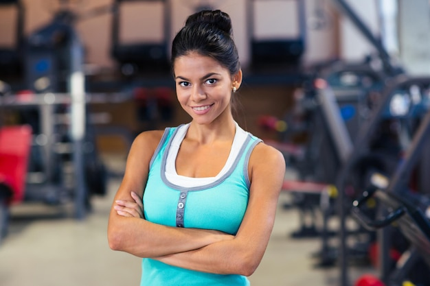 Ritratto di una donna sportiva allegra in piedi con le braccia incrociate in palestra
