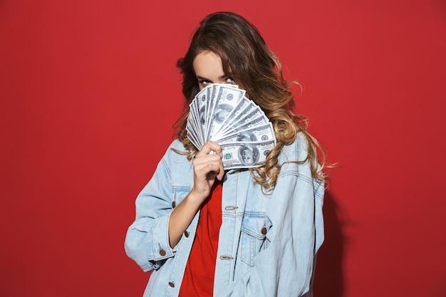 Ritratto di una giovane donna allegra ed elegante che indossa una giacca di jeans in piedi isolata sul muro rosso, in posa, mostrando banconote in denaro, faccia di copertina
