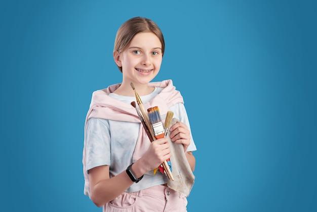 Ritratto di allegra ragazza adolescente con maglione avvolto intorno alle spalle tenendo i pennelli, lei frequenta la scuola d'arte