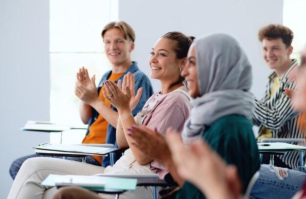 Un ritratto di allegro studente universitario seduto e studiando in aula al chiuso, applaudendo.