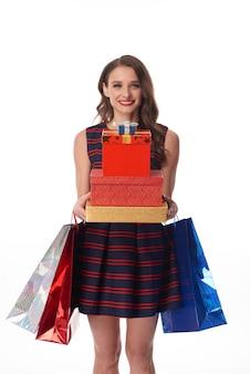 Ritratto di una ragazza allegra dai capelli ondulati in un bellissimo vestito in piedi con una pila di regali e borse su sfondo bianco