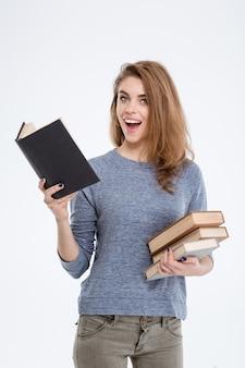 Ritratto di una donna allegra che tiene libri e guarda la telecamera isolata su uno sfondo bianco
