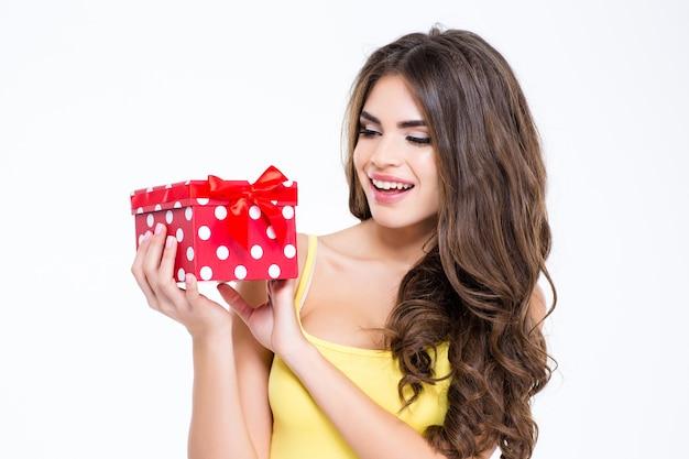 Ritratto di una donna allegra che tiene in mano una confezione regalo isolata su uno sfondo bianco