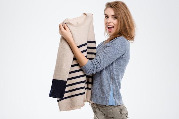 Ritratto di una donna allegra che tiene in mano un maglione isolato su uno sfondo bianco