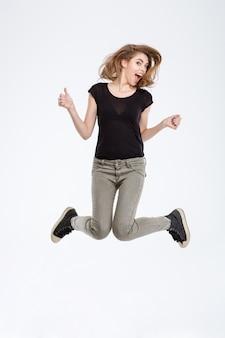 Ritratto di una donna allegra che salta isolata su uno sfondo bianco