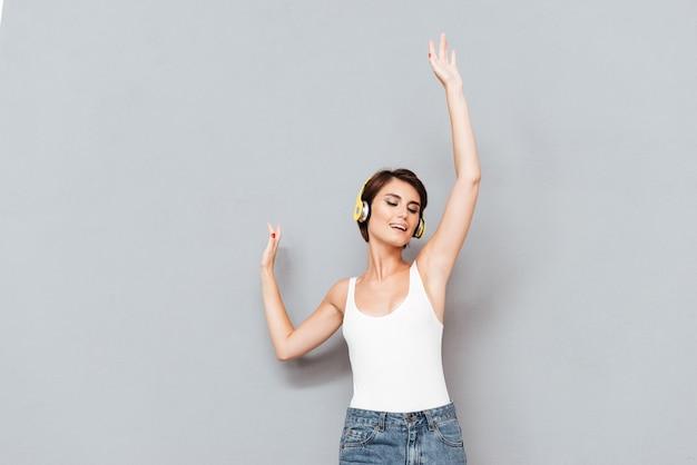 Ritratto di una donna allegra ascoltando musica in cuffia e cantando con le mani alzate in alto isolato su uno sfondo grigio