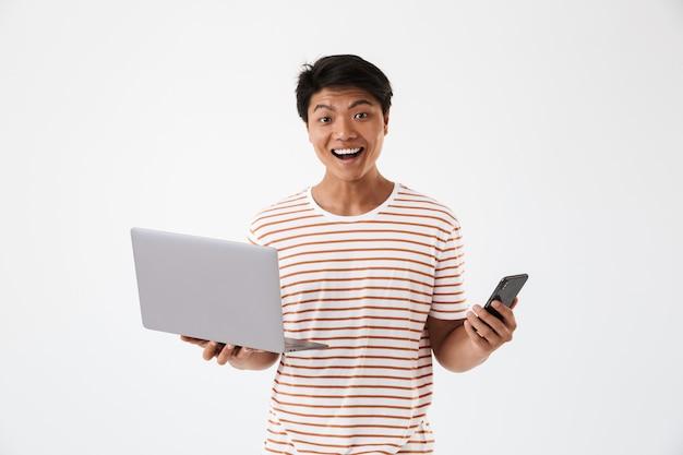 Ritratto di un allegro giovane uomo asiatico tenendo il computer portatile
