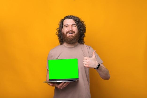 Ritratto di allegro giovane uomo barbuto sorridente e mostrando pollice in alto e laptop con schermo verde