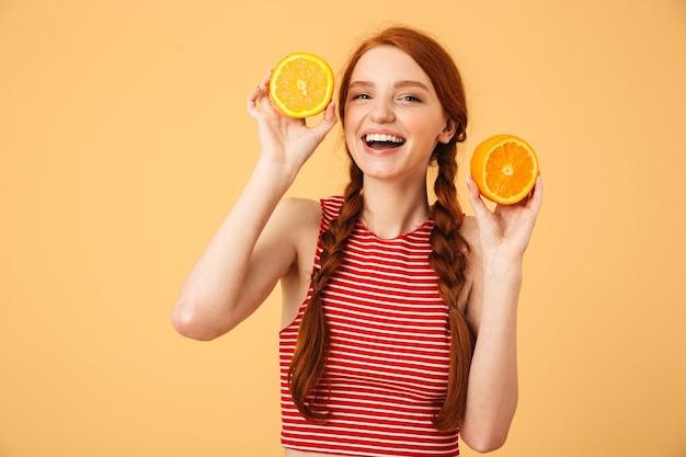 Ritratto di una giovane e bella donna allegra dai capelli rossi in posa isolata sul muro giallo che tiene l'arancia.