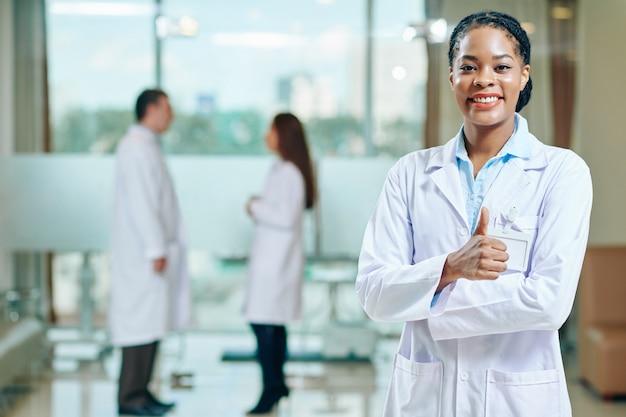 Ritratto di allegro giovane medico generico nero che mostra i pollici in su e che sorride alla parte anteriore