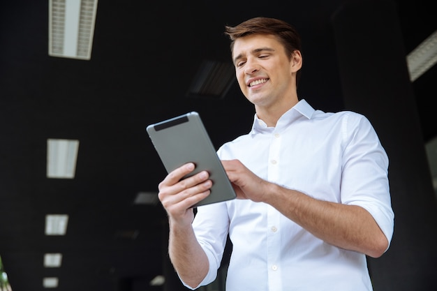 Ritratto di allegro giovane imprenditore utilizza lo smartphone e sorridente vicino al centro business