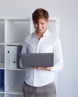 Ritratto di un giovane uomo d'affari allegro in camicia bianca che tiene in mano un computer portatile, isolato su uno sfondo bianco.
