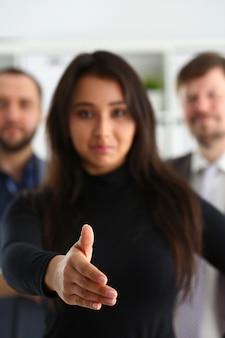 Ritratto di allegri giovani imprenditori in ufficio donna prestano la mano