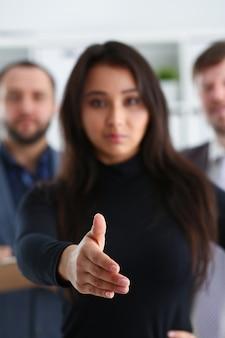 Il ritratto di giovani uomini d'affari allegri in donna dell'ufficio presta la mano