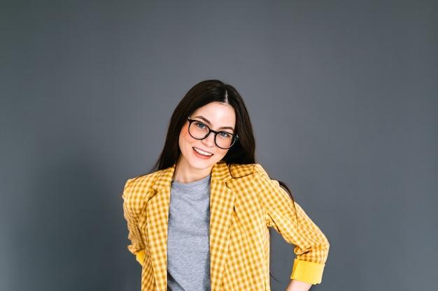 Ritratto di allegra giovane donna caucasica in occhiali da vista e tailleur
