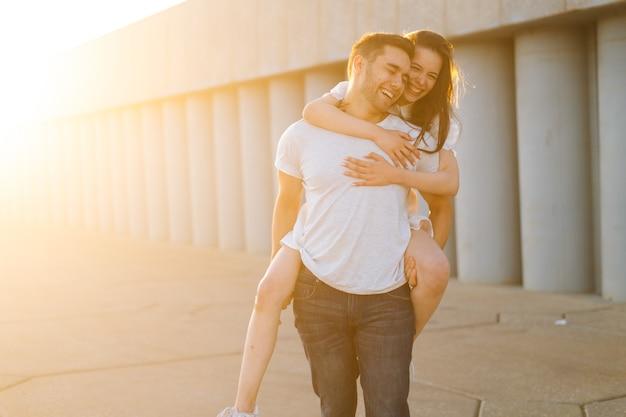 Ritratto di giovane coppia allegra divertirsi abbracciando e godersi l'ora legale insieme al tramonto su sfondo di luce solare intensa. felice coppia caucasica innamorata che ha una passeggiata romantica all'aperto.