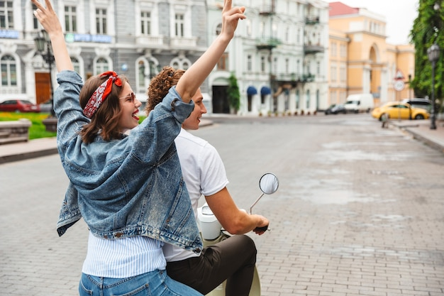 Ritratto di una giovane coppia allegra in sella a una moto insieme alla via della città