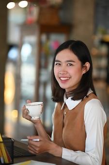 Ritratto di giovane donna allegra che tiene una tazza di caffè e sorridente